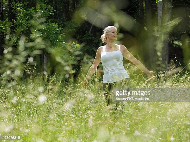 Woman walks through field of fresh grasses, forest