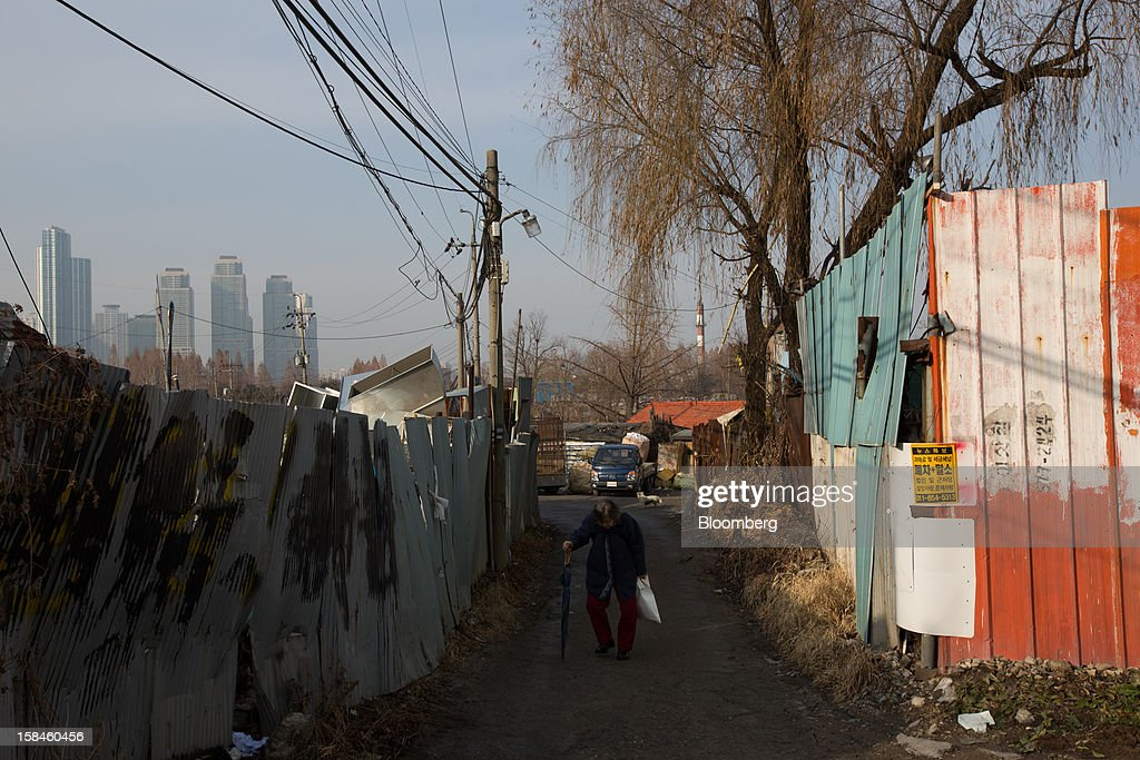 A woman walks through Guryong village as high rise residential buildings stand in the background in the Gangnam district of Seoul, South Korea, on Sunday, Dec. 16, 2012. South Koreans vote on Dec. 19 to replace President Lee Myung Bak, whose five-year term ends in February. Photographer: SeongJoon Cho/Bloomberg via Getty Images