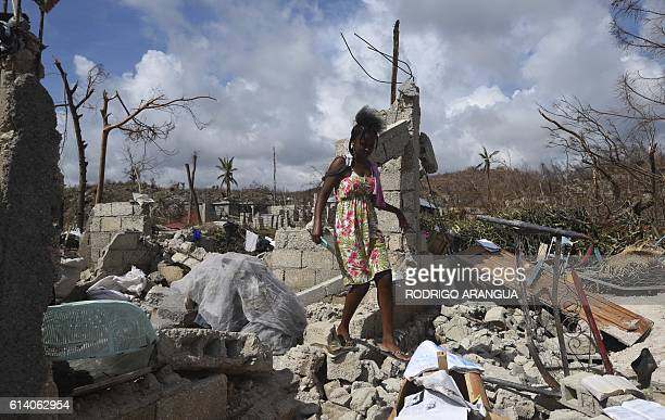 A woman walks through her home destroyed by Hurricane Matthew in Port Salut southwest of PortauPrince on October 11 2016 Haiti faces a humanitarian...