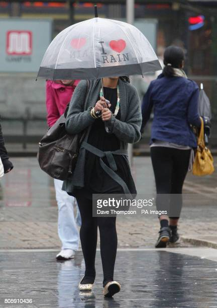 A woman walks through Manchester holding her umbrella as strong winds and rain hit Manchester city centre