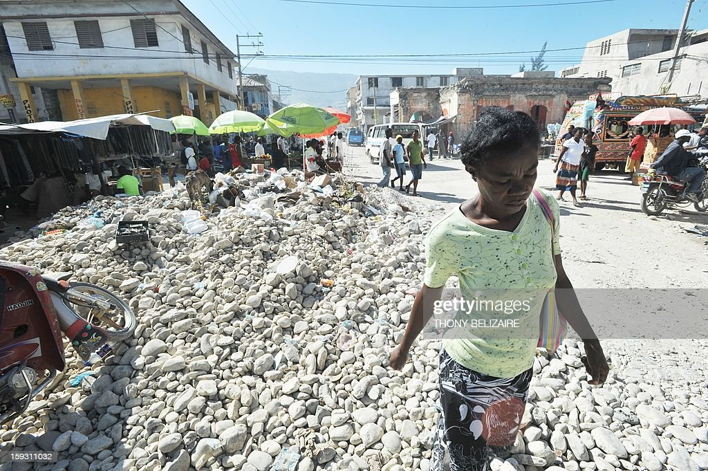 A woman walks through rubble in downtown Port-au-Prince on January 11, 2013. Three years after Haiti was devastated by a massive earthquake, hundreds of thousands of homeless people are still at risk from crime, disease and the elements in crowded makeshift camps. The 2010 disaster triggered a global outpouring of sympathetic rhetoric and pledges of aid for the already impoverished Caribbean nation, but residents and aid agencies complain that rebuilding and re-development has been too slow. Around 358,000 people are still living rough in scores of camps scattered around the capital Port-au-Prince and surrounding districts, exposed to a crime wave, a cholera outbreak and -- from time to time -- hurricanes. AFP PHOTO Thony BELIZAIRE
