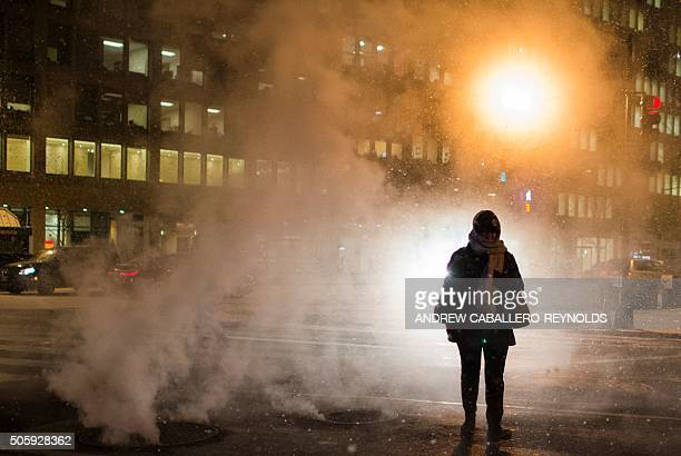 A woman walks through steam in a snow storm as she crosses the street in Washington DC on January 20 2016 / AFP / Andrew CaballeroReynolds