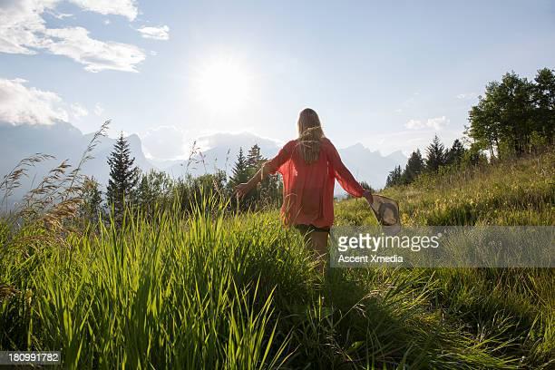 Woman walks through tall grasses, mountain meadiow