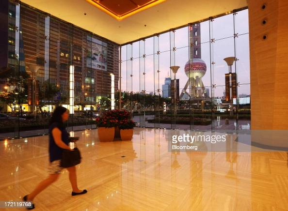A woman walks through the foyer of a commercial building as the Oriental Pearl Tower stands behind a glass window at dusk in the Lujiazui district of...