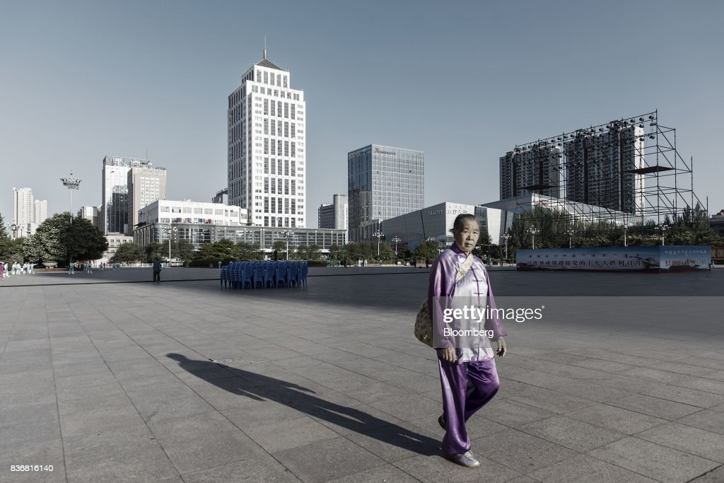 A woman walks through the main square in Baotou, Inner Mongolia, China, on Friday, Aug. 11, 2017. China's economy showed further signs of entering a second-half slowdown, as curbs on property, excess borrowing and industrial overcapacity began to bite. Photographer: Qilai Shen/Bloomberg via Getty Images