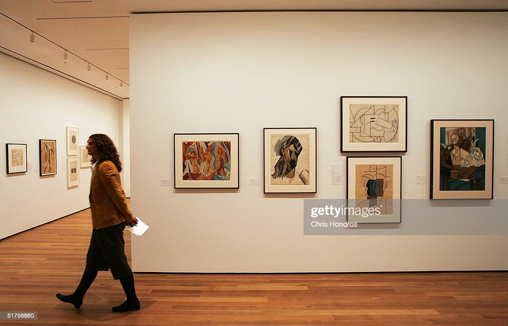 A woman walks through the photography collection in the new Museum of Modern Art building on 53rd Street November 17 2004 in New York City The new...