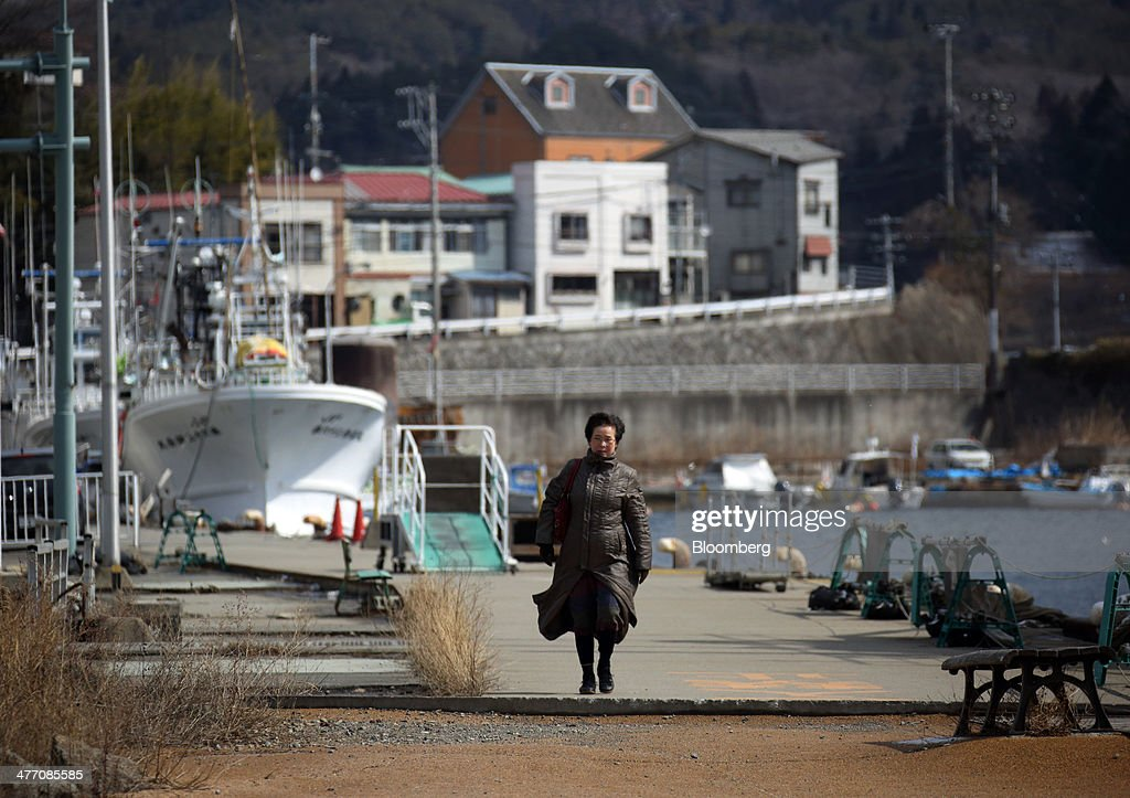 A woman walks through the port in Kesennuma City, Miyagi Prefecture, on Friday, March 7, 2014. Reconstruction of Tohoku, the northern Japan region devastated by the March 11, 2011 earthquake and tsunami, continues as the third anniversary of the disaster approaches. Photographer: Tomohiro Ohsumi/Bloomberg via Getty Images