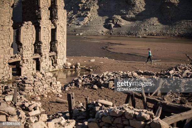 A woman walks through the remains of the former town of Mansilla on October 8 2016 after the village emerged from the depths of the Mansilla...