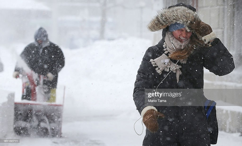 A woman walks through the snow as a worker clears snow from a sidewalk in the Back Bay neighborhood during a lingering blizzard on February 9, 2013 in Boston, Massachusetts. The powerful storm has knocked out power to 650,000 and dumped more than two feet of snow in parts of New England.