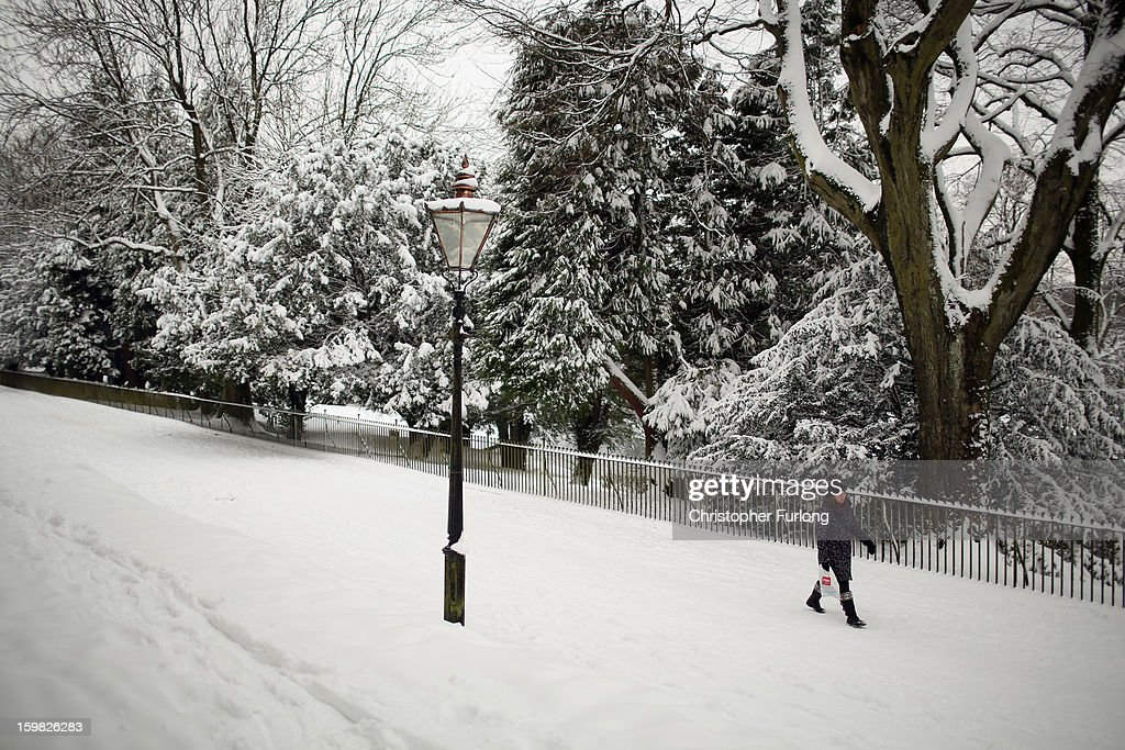A woman walks through the snow in The Pavilion Gardens on January 21, 2013 in Buxton, United Kingdom. The Met Office has issued a red weather warning for parts of the Uk and advising against all non-essential travel as up to 30cm of snow is expected to fall in some areas today. The adverse weather has closed nearly 5,000 schools and caused many airports to cancel flights.