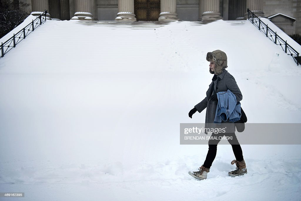 A woman walks through the snow past the National City Christian Church February 13, 2014 in Washington, DC. The DC area received its first significant winter storm beginning Wednesday night, February 12th, with continued mixed winter weather expected throughout Thursday. AFP PHOTO BRENDAN SMIALOWSKI