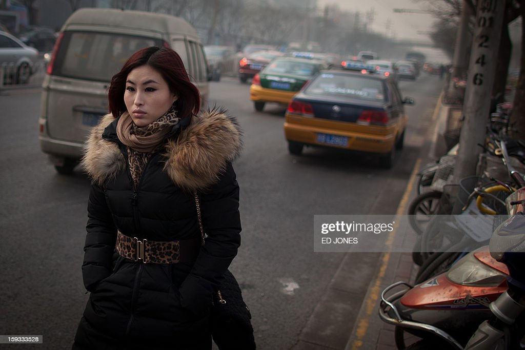 A woman walks through traffic on a road during severe pollution in Beijing on January 12, 2013. Air quality data released via the US embassy twitter feed recorded air quality index levels so hazardous that they were classed as 'Beyond Index'. Just after midday the particle matter (PM) 2.5 figure was 519 on a scale that stops at 500, and advises against all outdoor activity. AFP PHOTO / Ed Jones