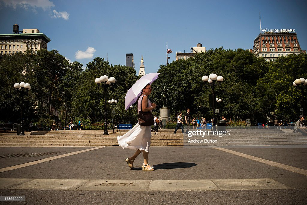 A woman walks through Union Square with a sun umbrella on July 16 2013 in New York City A stifling heat wave has descended upon the New York City...