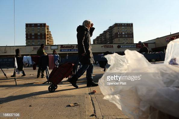 A woman walks to a free clothing distribution site near the beach in Rockaway on December 13 2012 in New York City Much of the Rockaway neighborhood...
