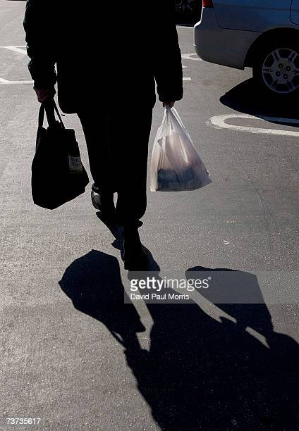A woman walks to her car with groceries in plastic bags at a Safeway store on March 28 2007 in San Francisco California The Board of Supervisors in...