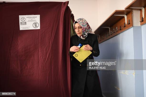 TOPSHOT A woman walks to the ballot box to place her vote in the referendum on expanding the powers of the Turkish president on April 16 2017 in...