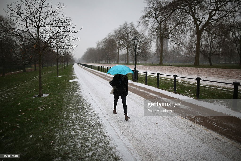 A woman walks to work through Hyde Park as snow dusts the ground on January 18, 2013 in London, England. Severe weather is expected in parts of the United Kingdom today.