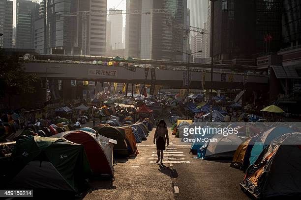 A woman walks to work through the Admiralty protest site on November 18 2014 in Hong Kong Hong Kong Baliffs oversaw the removal of some barricades...