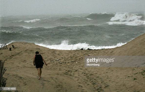 A woman walks towards the Atlantic Ocean in Buxton North Carolina US on Friday Aug 26 2011 Hurricane Irene made landfall on the North Carolina coast...