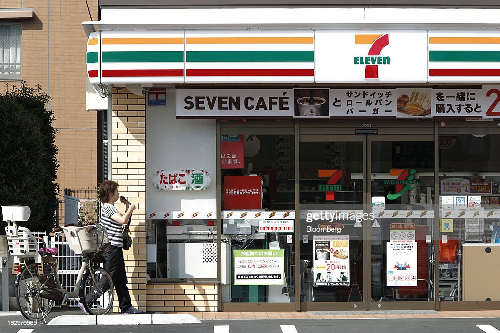 A woman walks towards the entrance of a 7-Eleven convenience store, operated by Seven & I Holdings Co., in Soka, Saitama Prefecture, Japan, on Thursday, Oct. 3, 2013. Seven & I reported a 25 percent rise in first-half net income, in line with analysts' estimates. Photographer: Kiyoshi Ota/Bloomberg via Getty Images