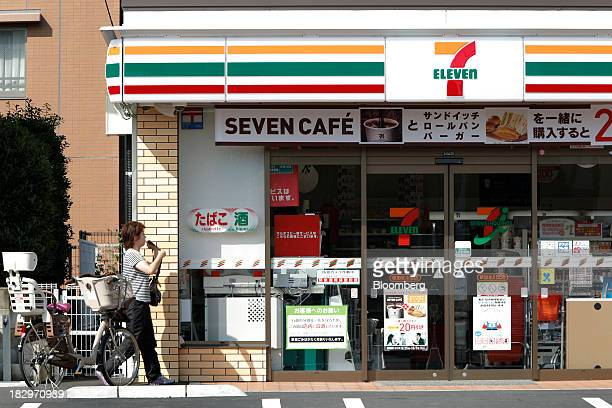 A woman walks towards the entrance of a 7Eleven convenience store operated by Seven I Holdings Co in Soka Saitama Prefecture Japan on Thursday Oct 3...