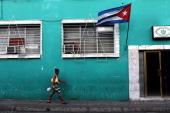 A woman walks under a Cuban flag on March 22 2012 in Santiago de Cuba Cuba Fourteen years after Pope John Paul II visited Cuba Pope Benedict is...