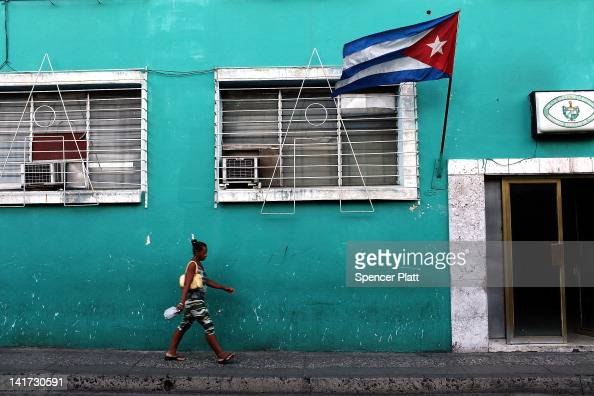 A woman walks under a Cuban flag on March 22 2012 in Santiago de Cuba Cuba Fourteen years after Pope John Paul II visited Cuba Pope Benedict is...
