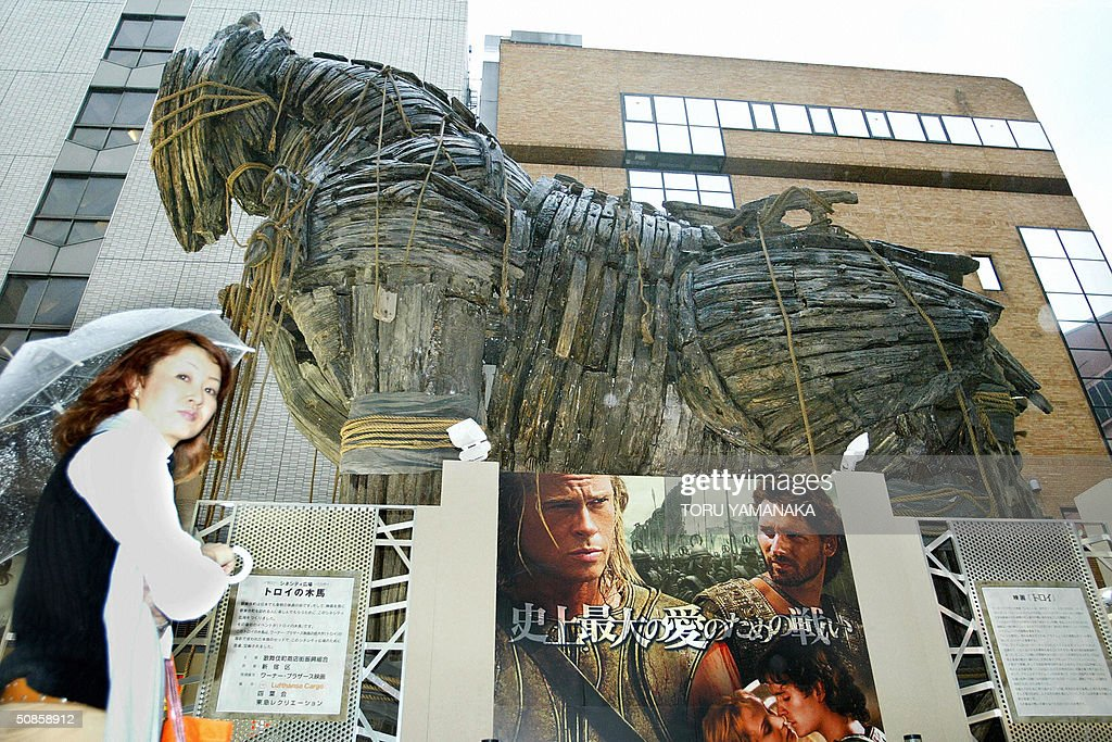 A woman walks under a Trojan Horse which was used in the American movie 'Troy' in Kabuki-cho entertainment district of Tokyo, 20 May 2004. The 11-meter tall and 14-meter long wooden horse was exhibited for the promotion of the film which will be screenned in Japan from this weekend. AFP PHOTO/Toru YAMANAKA