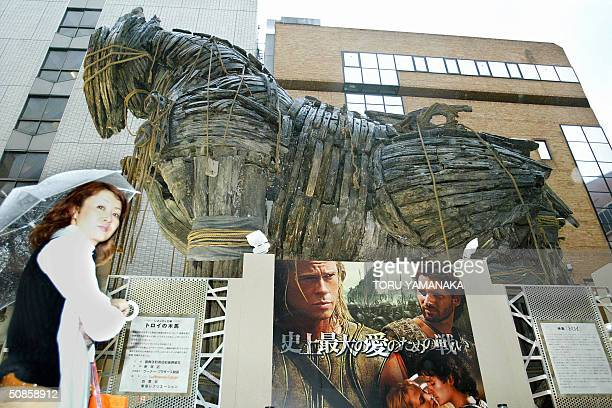 A woman walks under a Trojan Horse which was used in the American movie 'Troy' in Kabukicho entertainment district of Tokyo 20 May 2004 The 11meter...