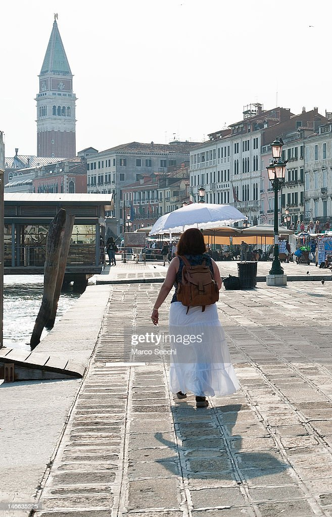 A woman walks under an umbrella on Riva degli Schiavoni on June 21, 2012 in Venice, Italy. An intense heatwave is sweeping across many regions in Italy, prompting the country's health ministry to issue a number of high level alerts.