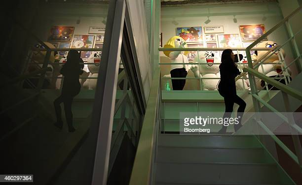 A woman walks up stairs past Line Corp character toys and merchandise on display at the Line Friends Store in Tokyo Japan on Thursday Dec 10 2014...