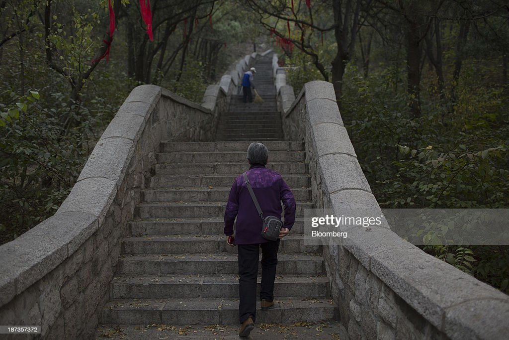 A woman walks up steps at Thousand Buddha Mountain in Jinan, China, on Wednesday, Nov. 6, 2013. The third plenary session of the 18th Communist Party of China Central Committee will be held from Nov. 9 to Nov. 12 in Beijing. Photographer: Brent Lewin/Bloomberg via Getty Images