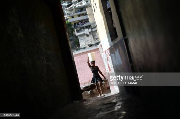 A woman walks with a bucket of water on her head on the streets of Jalousie neighborhood in the commune of Petion Ville PortauPrince on June 20 2017...