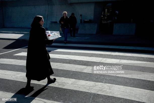 A woman walks with a cake to the international arrivals hall at Washington Dulles International Airport February 6 2017 in Dulles Virginia / AFP /...