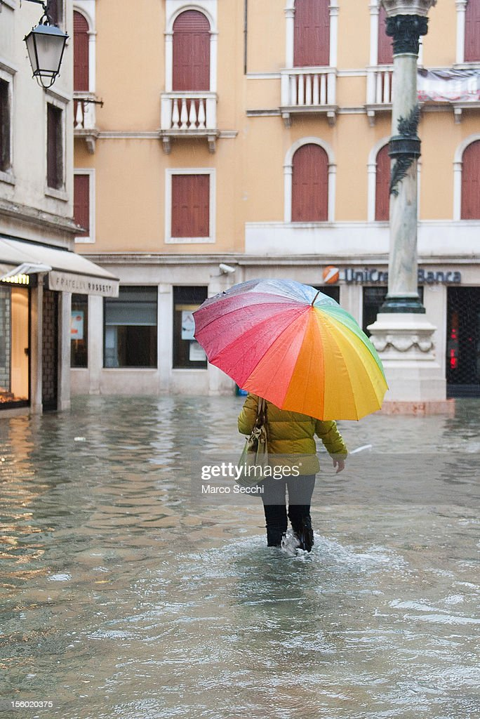 A woman walks with a coloured umbrella behind Rialto during the exceptional High Water on November 11, 2012 in Venice, Italy. More than 70% of Venice has been been left flooded, after the historic town was hit by exceptionally and unexpected high tide. The sea level rose very quickly to 150 due as well to strong southerly wind and heavy rain.