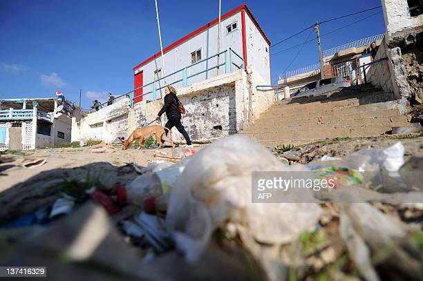 A woman walks with a dog in front of garbage gathered on Tamentfoust beach on January 20 east of Algiers during a cleanup operation AFP PHOTO/FAROUK...