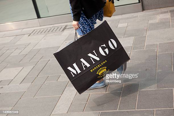 A woman walks with a Mango branded shopping bag in Beijing China on Monday May 7 2012 Chinese Premier Wen Jiabao cut the annual growth rate target to...