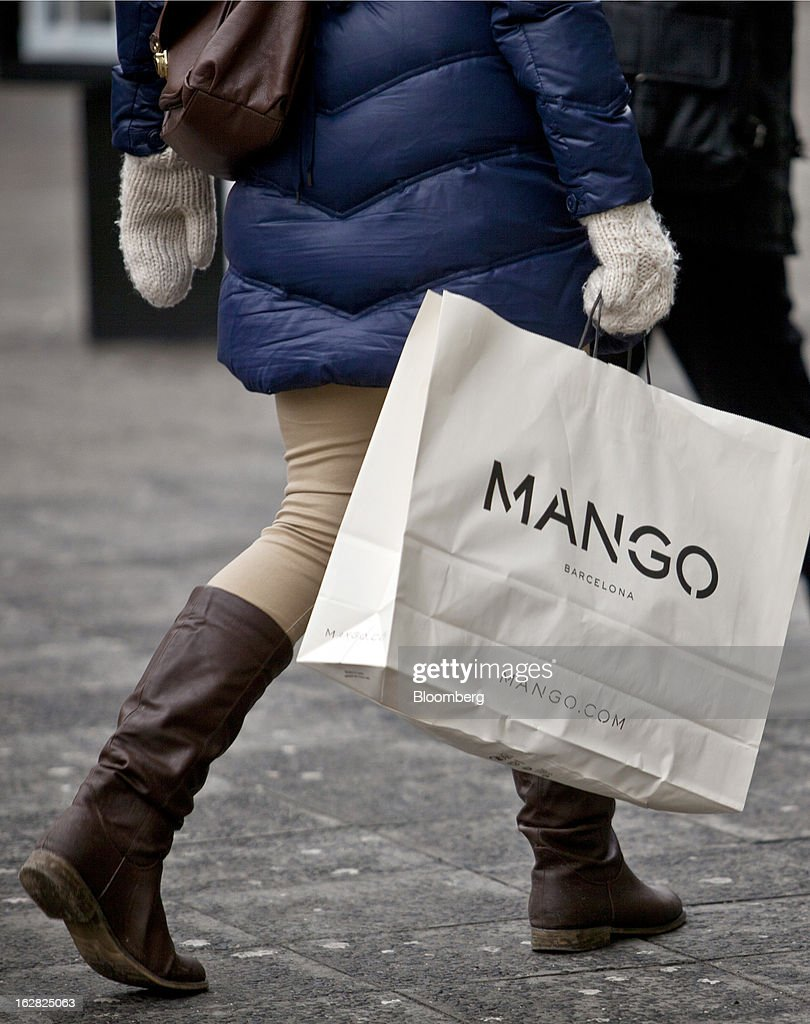 A woman walks with a Mango branded shopping bag in Berlin, Germany, on Wednesday, Feb. 27, 2013. German unemployment unexpectedly fell in February amid signs that Europe's biggest economy is returning to growth after a contraction at the end of last year. Photographer: Balint Porneczi/Bloomberg via Getty Images