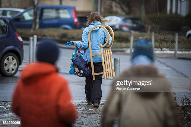 A woman walks with a sledge over the shoulder during thaw on January 12 2017 in Berlin Germany