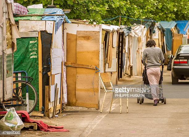 A woman walks with a stroller on June 13 2015 at a Roma camp in Lille northern France where David a 4yearold Roma boy died in a fire on June 8 during...