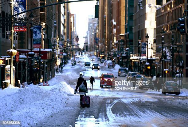 TOPSHOT A woman walks with a suitcase down a snowcovered street in New York City on January 24 2016 A massive blizzard that claimed at least 16 lives...