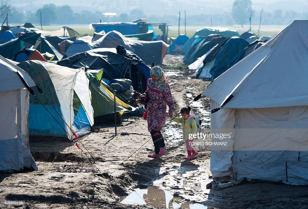A woman walks with a young girl down a muddy path among tents at a makeshift camp for migrants and refugees near the village of Idomeni, not far from the Greek-Macedonian border, on April 30, 2016. Some 54,000 people, many of them fleeing the war in Syria, have been stranded on Greek territory since the closure of the migrant route through the Balkans in February. / AFP / TOBIAS