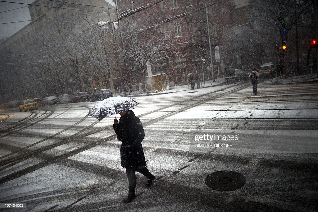 A woman walks with an umbrella as the first snow fall covers Sofia on December 3, 2012. AFP PHOTO / DIMITAR DILKOFF