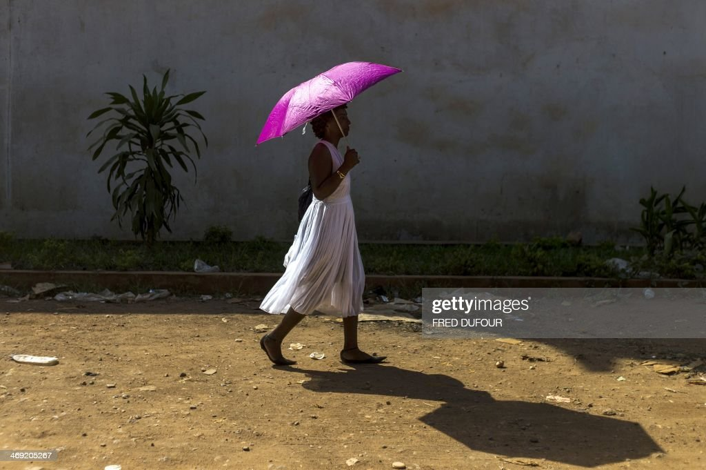 A woman walks with an umbrella in the centre of Bangui, Central African Republic, on February 13, 2014. The impoverished Christian-majority country descended into chaos in March 2013 after a coup by the mainly-Muslim Seleka rebellion overthrew the government, sparking deadly violence that has uprooted a million people out of a population of 4.6 million.