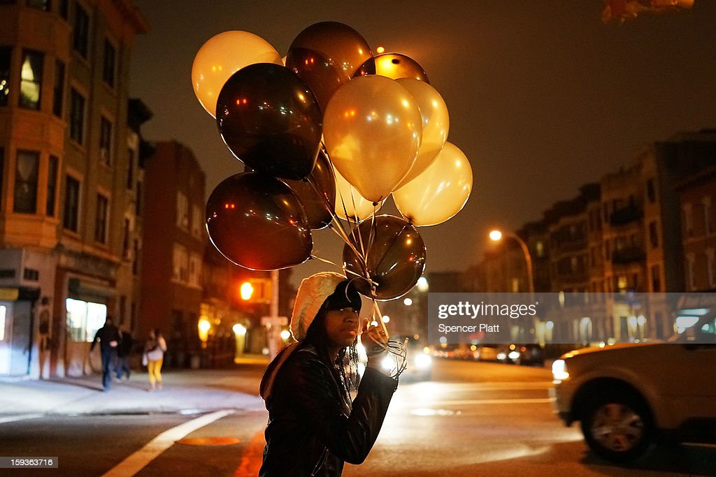 A woman walks with balloons near where a rally and vigil was held at the location where a 16-year-old boy was shot last Tuesday evening, on January 12, 2013 in the Crown Heights neighborhood of the Brooklyn borough of New York City. The gathering was sponsored by the local group S.O.S., which is a community-based effort to end gun violence. S.O.S. holds the gatherings at all shooting locations in Crown Heights to draw attention to the violence and to encourage a community response to the shootings. While murders were down for 2012 in New York City, gun violence continues to plague many communities.