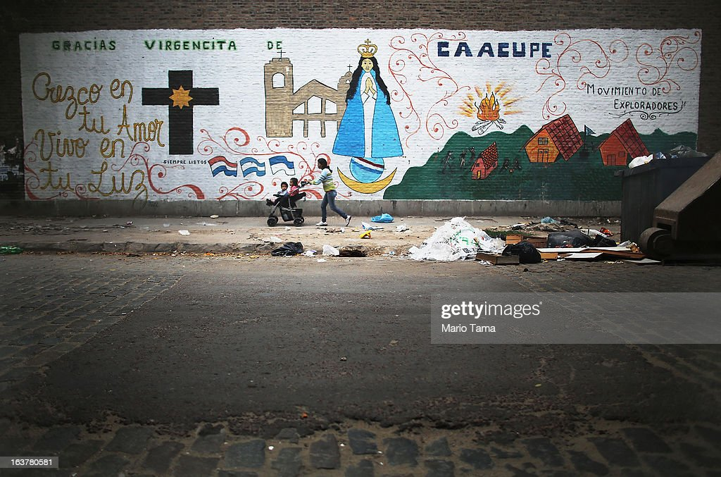 A woman walks with children past a mural near the Virgin of the Miracles of Caacupe church in the Villa 21-24 slum, where archbishop Jorge Mario Bergoglio, now Pope Francis, used to perform charity work, on March 15, 2013 in Buenos Aires, Argentina. Francis was the archbishop of Buenos Aires and is the first Pope to hail from South America. Some locals are now affectionately calling Francis, known for his charity work in the slums, the 'slum pope.'