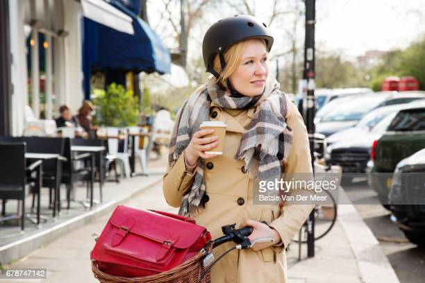Woman walks with coffee and bike in urban street on way to work.