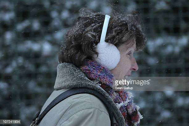 A woman walks with earmuffs through a gentle snowfall in wintery Zehlendorf district on December 2 2010 in Berlin Germany The German capital was hit...