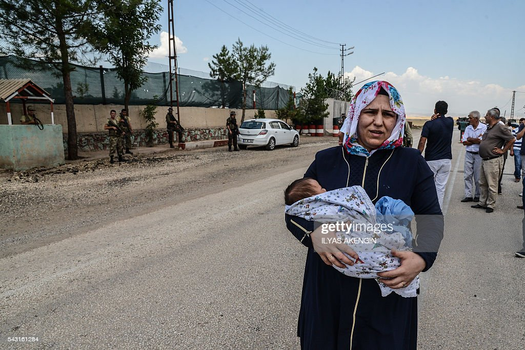 A woman walks with her baby as Turkish soldiers block the road at a military check point as Members of Parliament of the pro-Kurdish Peoples' Democratic Party (HDP) and kurdish activists wait in a military check point as they want to enter Lice district in Diyarbakir on June 26, 2016. Militants from the outlawed Kurdistan Workers Party (PKK) on June 24, 2016 killed six Turkish soldiers in two separate attacks in the troubled southeast of the country, the army said. / AFP / ILYAS