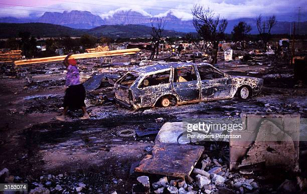 A woman walks with her belongings past a burned out car a day after a shack fire on January 19 in a poor township outside Strand South Africa Shack...